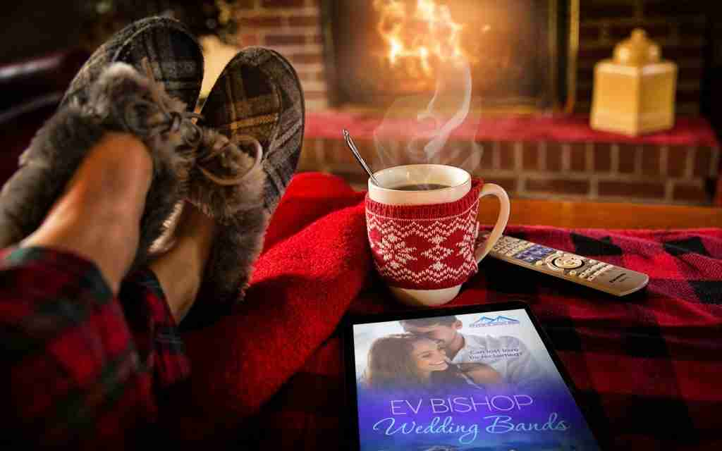 Photo of Wedding Bands novel by Ev Bishop, a mug of tea, and a cozy fire