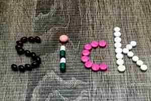 Sign that says SICK, spelled in pills