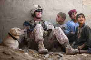 Soldier surrounded by children.
