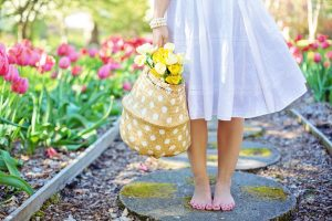Photo of young woman walking along a garden path