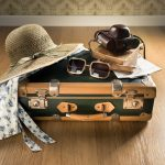Vintage traveler suitcase with sunglasses straw hat old camera and maps.